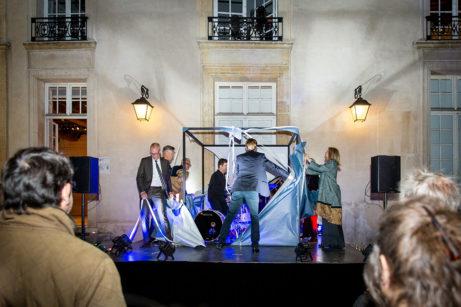 Guldpalmsvinnaren Ruben Östlund, statssekreterare Oscar Stenström och övriga invigningstalare öppnar det stora paketet med slagverkare Niklas Brommare. Foto: Luca Lomazzi