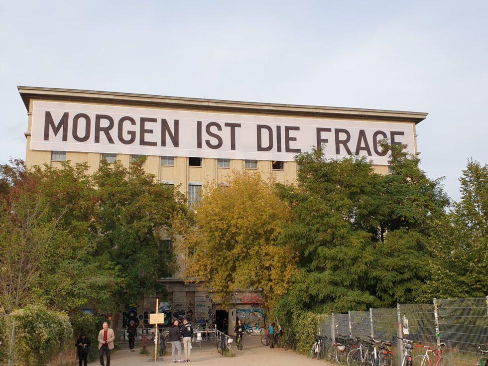 """Bilden visar en stor funktionalistisk byggnad med träd framför. På fasaden hänger en stor banderoll med texten """"Morgen ist die Frage""""."""