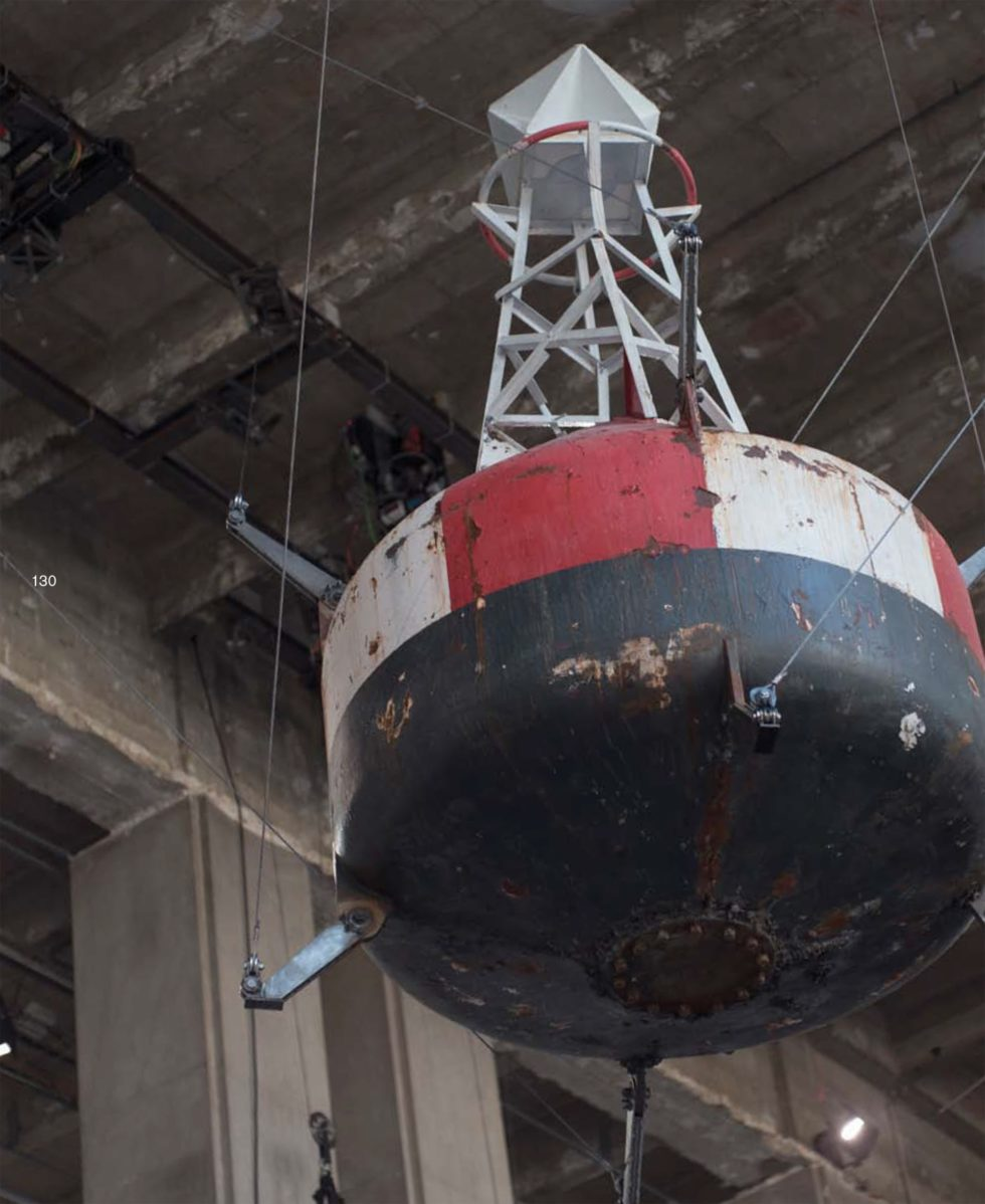 Bilden visar en stor stålboj i svart, vitt och rött som hänger i taket på en industribyggnad.