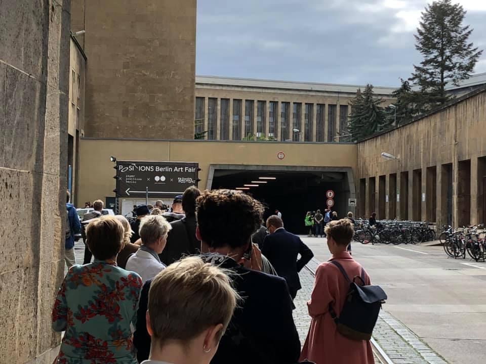 Bilden visar människor i en kö utanför en funktionalistisk byggnad.