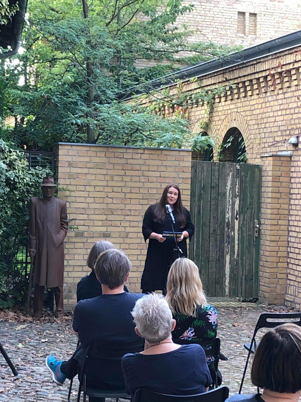 Bilden visar kulturrådet Nina Katarina Karlsson som talar inför en publik på en stenlagt innergård.