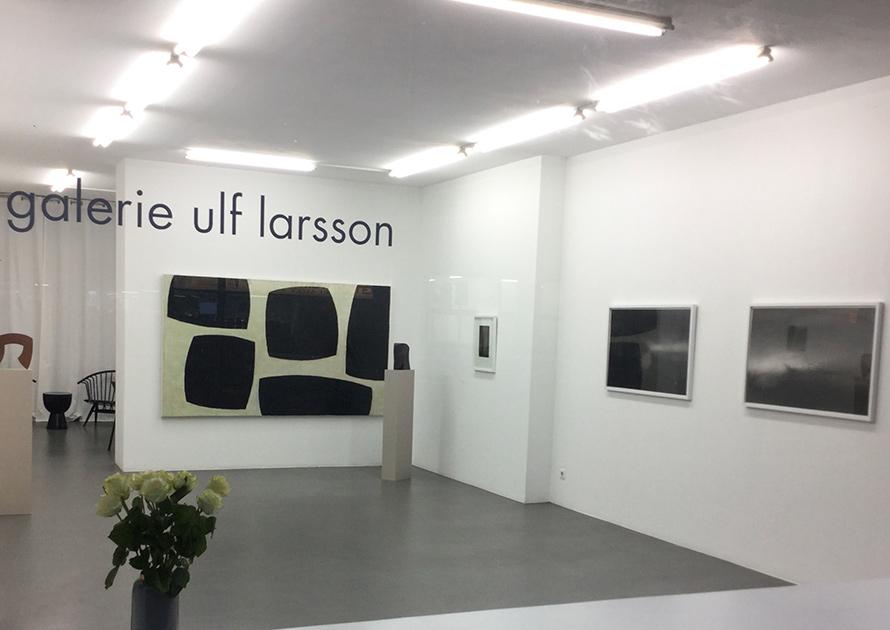 Bilden visar ett abstrakt konstverk med stora svarta fält på en vit vägg i ett galleri.