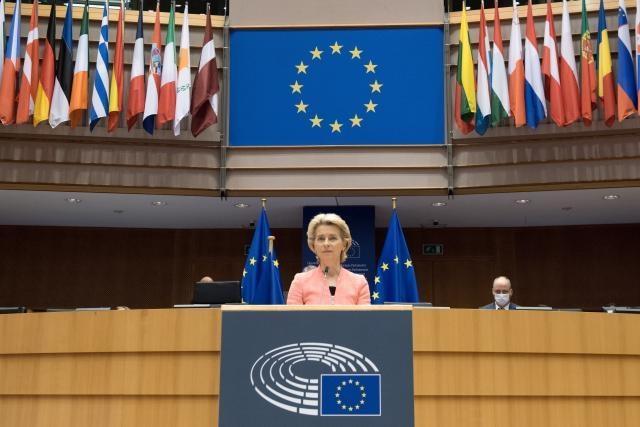 Ursula von der Leyen står vid Europaparlamentets podium framför EU:s och medlemsstaternas flaggor.