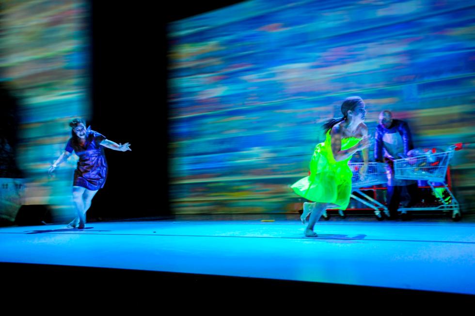 Bilden föreställer två kvinnliga skådespelare som springer över scenen. I bakgrunden syns en manlig skådespelare i slaktarförkläde och två kundvagnar.