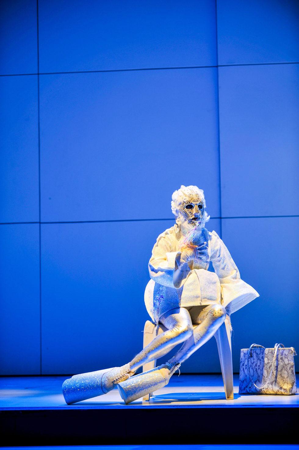 Bilden föreställer en skådespelerska i guld- och glitterkläder med juvelprydd ansiktsmask och extrema platåskor mot en blå bakgrund.