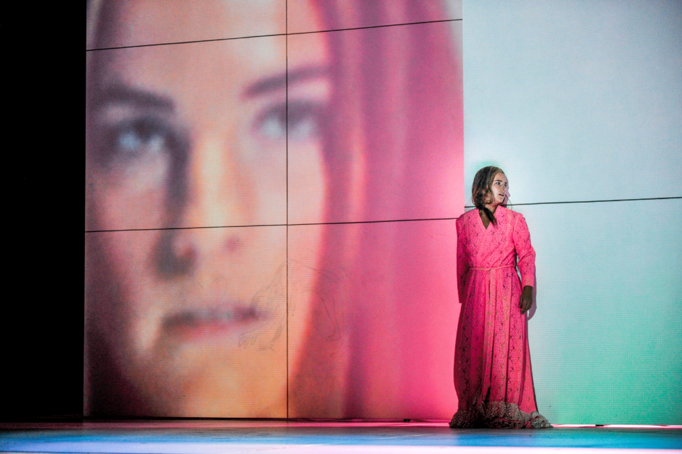 Bilden föreställer en skådespelare i rosa klänning framför en projicerad storbild av skådespelarens ansikte.