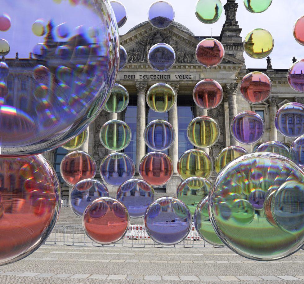 Bilden föreställer Earth Speakers färgglada bubblor i blått, rött, grönt och gult vid riksdagshuset i Berlin