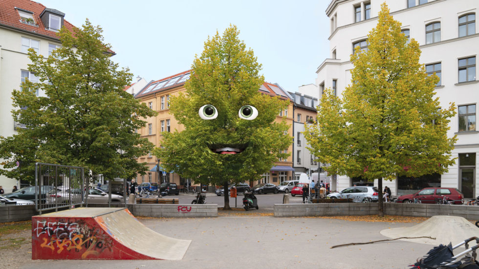 Bilden föreställer ett träd i urban miljö med ögon och mun.