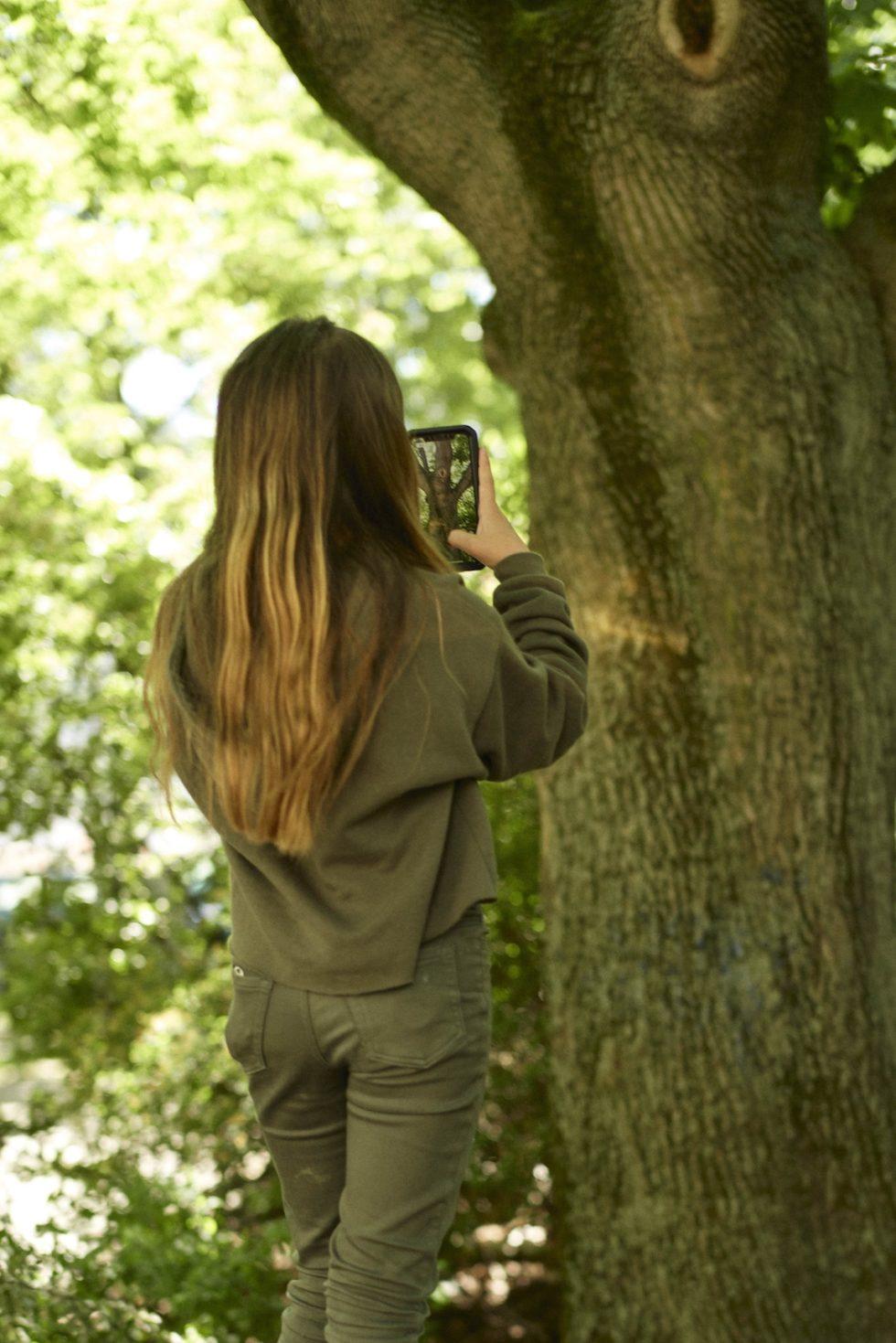 Bilden visar en flicka bakifrån med gröna kläder och långt hår när hon använder appen på ett träd.