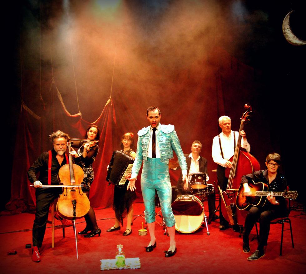 Lindy Larsson Forss i turkos kostym tillsammans med de sex musikerna i bandet, som spelar cello, fiol, dragspel, trummor, bas och gitarr.
