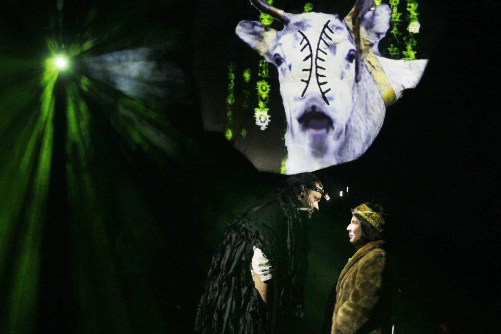 Bilden föreställer en svartklädd manlig skådespelare som böjer sig ner mot en kvinna i päls. I bakgrunden syns ett grön ljus och en bild av en vit kalv.