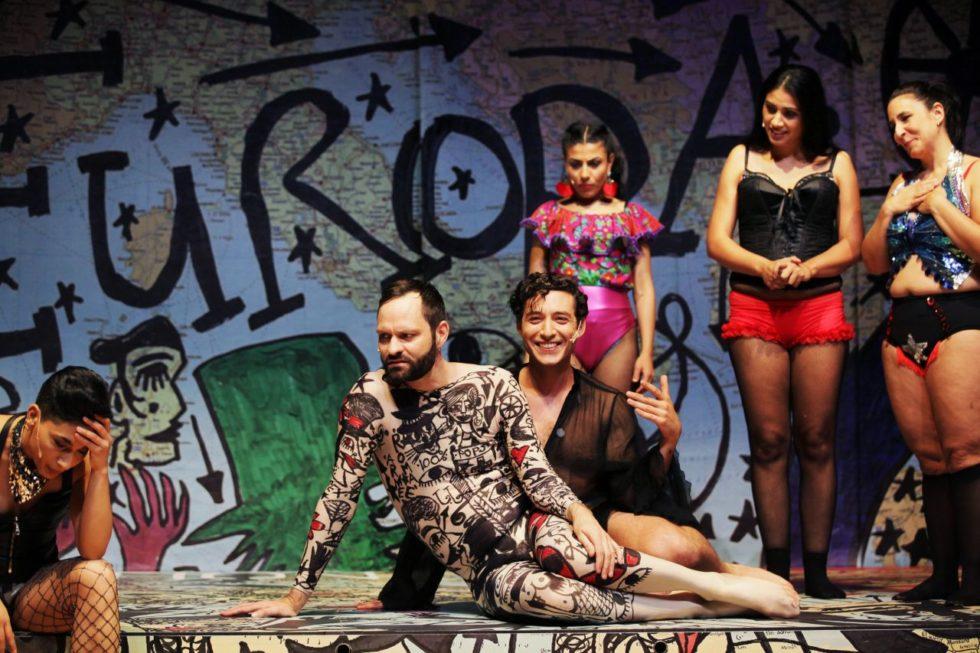 Bilden föreställer sex skådespelare i pjäsen Roma Armee. I mitten av bilden sitter Lindy Larsson Fors i en kroppsstrumpa med svart grafitti. Bakgrunden består av en nedklottrad Europakarta.