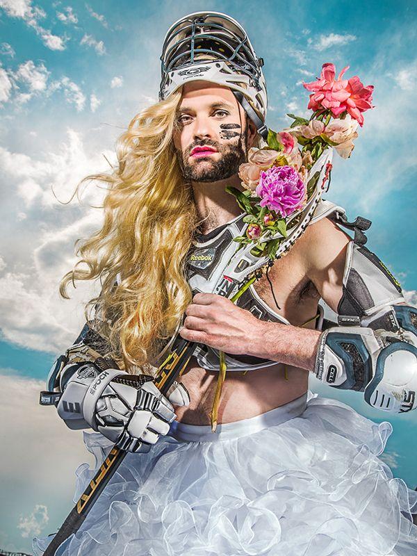 Bilden föreställer en man med långt lockigt ljust hår iklädd hjälm och armbågs- och bröstskydd samt en vit tyllkjol. I handen håller han ett redskap där stora blommor är fästade.