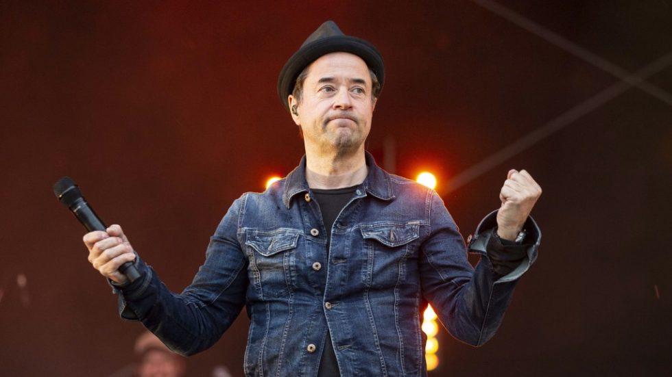 Bild på skådespelaren med en mikrofon i ena handen. Han är klädd i jeansjacka och hatt.