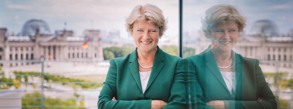 Ett foto på kulturministern i grön kavaj. I bakgrunden syns det tyska riksdagshuset.
