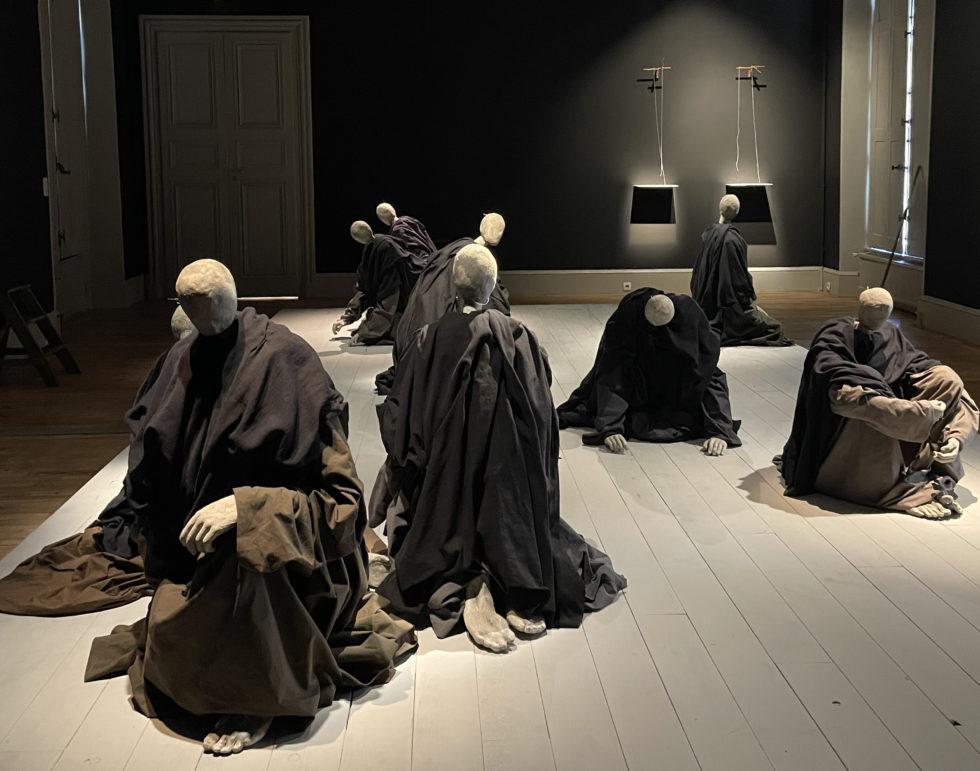 Nio figurer utan ansikten insvepta i mörkt tyg sitter på en träplatta och böjer sig åt olika håll