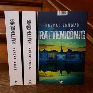 Bild på två bokryggar samt ett blågrönt bokomslag med en bild av Stockholm.