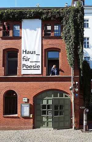 """Bild på ett rött tegelhus med en grön port och en fasadvepa med texten """"Haus für Poesie""""."""