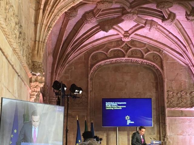 Margaritis Schinas håller ett tal i ett hörn av Hieronymusklostrets korsgång framför skärmar och europeiska flaggor.