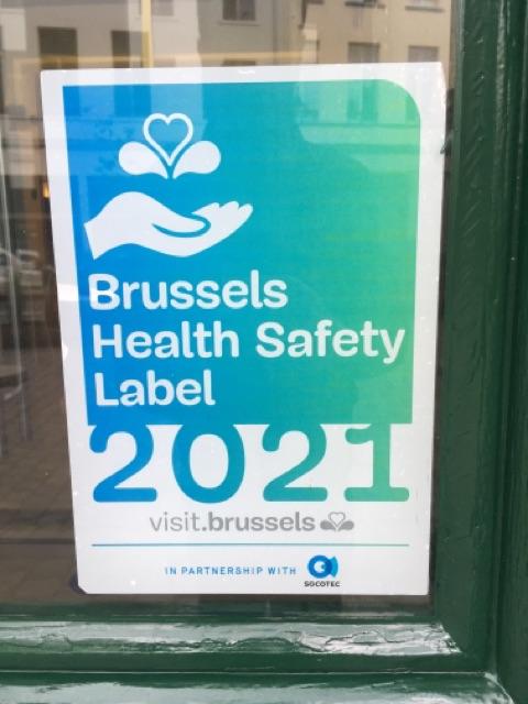 """Ett klistermärke på en entrédörr med texten """"Brussels Health Safety Label 2021""""."""