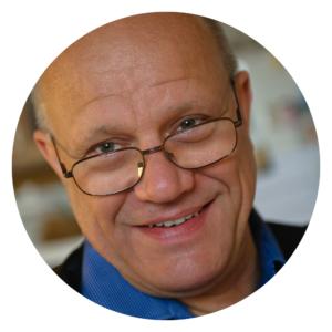 Porträtt på en man med glasögon och blå skjortkrage.
