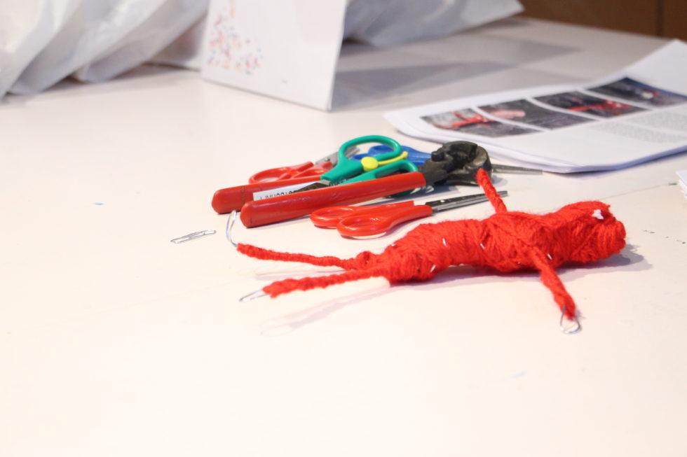 Foto på en röd garnfigur, saxar och tänger för att klippa ståltråd.