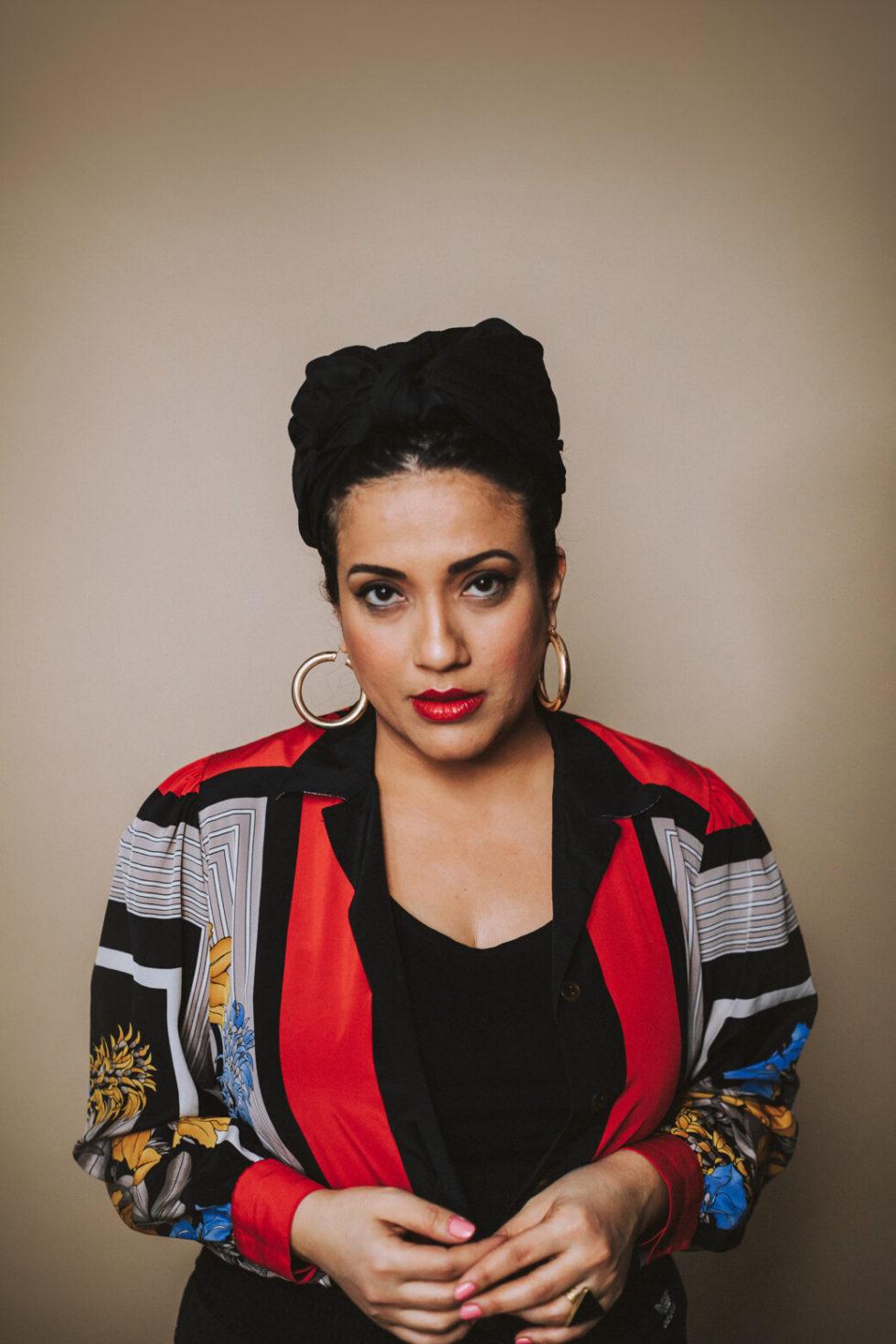 Foto av författaren med uppsatt svart hår, stora guldringar i öronen och iklädd en mönstrad blus i svart, rött och blått.