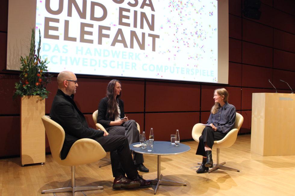 Foto med tre samtalande personer sittande i fåtöljer framför ett litet bord i auditoriet i den nordiska ambassadernas Felleshus.