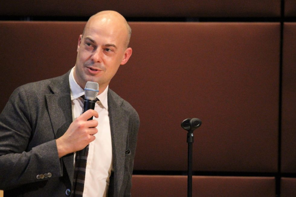 En man med rakat huvud i grå kavaj talar i mikrofon mot en vinröd bakgrund i auditoriet på Felleshuset.