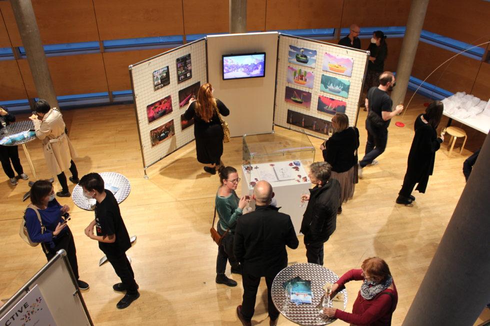 Foto tagit uppifrån trapporna ner på utställningsbesökarna. Skisser visas på utställningsväggarna och filmer med intervjuer av speldesigner visas på bildskärmar.